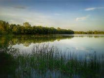 Reflexionssolnedgång i vatten Arkivfoton