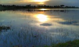 Reflexionssolnedgång i vatten Arkivbild