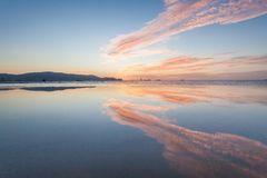 Reflexionssoluppgång eller solnedgångsikt med det orange molnet och blå himmel Arkivfoto