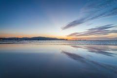 Reflexionssoluppgång eller solnedgångsikt med det orange molnet och blå himmel Arkivbild