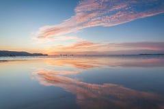 Reflexionssoluppgång eller solnedgångsikt med det orange molnet och blå himmel Arkivfoton