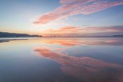Reflexionssoluppgång eller solnedgångsikt med det orange molnet och blå himmel Royaltyfria Bilder