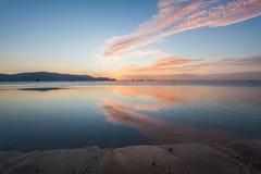 Reflexionssoluppgång eller solnedgångsikt med det orange molnet och blå himmel Royaltyfri Bild
