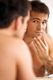 Reflexão do homem novo no espelho com mão no queixo Imagens de Stock