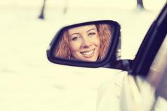 Reflexão feliz do motorista da mulher no espelho da opinião lateral do carro Viagem segura do inverno, viagem que conduz o concei Fotografia de Stock Royalty Free