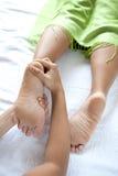 Reflexologist donnant à cliente de femme un massage de pied Image stock