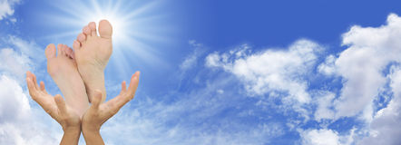 Reflexology blue sky banner. Website banner for a reflexologist showing female hands cupped under pair of feet on a blue sky and fluffy cloud background Royalty Free Stock Images