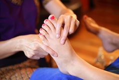 Reflexology foot massage, spa foot treatment by wood stick Royalty Free Stock Photos