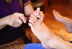 Reflexology foot massage, spa foot treatment by wood stick Royalty Free Stock Photo