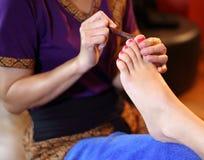 Reflexology foot massage, spa foot treatment by wood stick Stock Photo