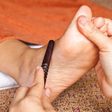 Reflexology foot massage by stick wood Royalty Free Stock Photography