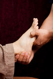 Reflexology pressure points. A massage therapist applies pressure to a foot point stock photos
