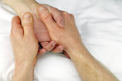 Reflexology Treatment. Male massage therapist hands massaging the hand of another man near the wrist Royalty Free Stock Image