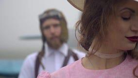 Refocus com um piloto farpado em um capacete 60s em uma mulher em um vestido e em um chapéu cor-de-rosa, movimento lento vídeos de arquivo