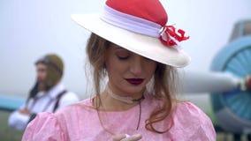 Refocus com um piloto plano idoso em uma mulher em um vestido cor-de-rosa e em um chapéu ao estilo do movimento 60s lento vídeos de arquivo