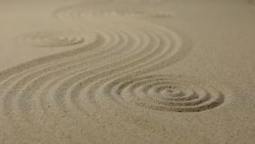 Refocusing the focus from the front circle to the far circle. Zen garden wit simple flowing waves and concentric circles