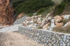 Reforçando a parede de pedra da alvenaria em uma praia Foto de Stock