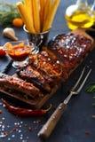 Reforços assados deliciosos temperados com um molho de aspersão picante e servidos com desbastado Imagem de Stock