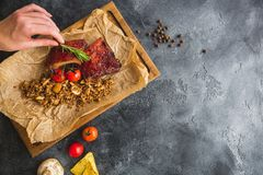 Reforços assados, trigo mourisco com cogumelo e tomates na placa de corte de madeira e na mão fêmea alimento e fundo Configuração Fotografia de Stock