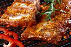 Reforços de carne de porco crus na grade Fotografia de Stock