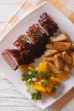 Reforços de carne de porco do BBQ com close-up da batata em uma placa Vista superior vertical Imagem de Stock