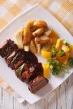 Reforços de carne de porco do BBQ com close-up dos vegetais em uma placa Parte superior vertical Imagens de Stock