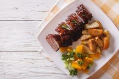 Reforços de carne de porco do BBQ com vegetais em uma placa vista superior horizontal Foto de Stock Royalty Free