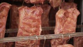Reforços de carne fumado, grelhados da carne em um armazenamento em uma fábrica industrial do processamento de carne vídeos de arquivo