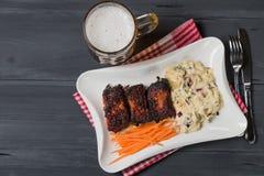 Reforços de carne de porco com salada, a cenoura e aipo americanos de batata Petisco da cerveja A vista da parte superior Cópia-e Foto de Stock
