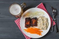 Reforços de carne de porco com salada, a cenoura e aipo americanos de batata Petisco da cerveja A vista da parte superior Cópia-e Fotografia de Stock