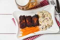 Reforços de carne de porco com salada, a cenoura e aipo americanos de batata Petisco da cerveja A vista da parte superior Cópia-e Fotografia de Stock Royalty Free