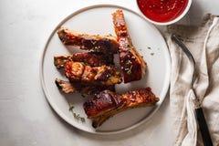 Reforços de carne de porco do BBQ com molho de pimentão na placa branca Reforços de carne de porco no fundo da ardósia Copie o es imagens de stock