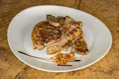 Reforços de carne de porco Roasted, decorados com microplaquetas da cebola em uma placa branca em um fundo de madeira imagens de stock