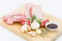 Reforços e alho crus de carne de porco em uma placa de corte imagens de stock