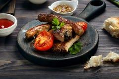 Reforços e salsichas de carne de porco grelhados servidos com tomate e molhos na tabela de madeira fotos de stock