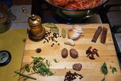 Reforços, ervas e especiarias crus do cordeiro na placa de corte de madeira, moedor da especiaria do vintage fotografia de stock