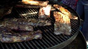 Reforços laterais da carne de porco que cozinham em um grande BBQ fora no fest do alimento de A vídeos de arquivo