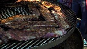 Reforços laterais da carne de porco que cozinham em um grande BBQ fora no fest do alimento de A filme