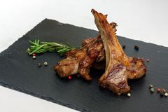 Reforços Roasted do cordeiro com alecrins e pimenta na placa preta Imagem de Stock Royalty Free