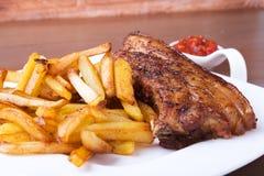 Refor?os de carne de porco grelhados com a batata livre e o molho na placa branca imagens de stock