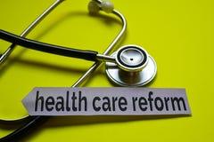 Reforma de la atención sanitaria del primer con la inspiración del concepto del estetoscopio en fondo amarillo fotografía de archivo
