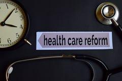 Reforma dos cuidados médicos no papel da cópia com inspiração do conceito dos cuidados médicos despertador, estetoscópio preto fotografia de stock