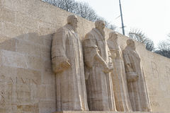 Reformation wall in Geneva. Statues on Reformation wall in Geneva, Switzerland. From left to right: William Farel, John Calvin, Theodore de Beze and John Knox Stock Photo