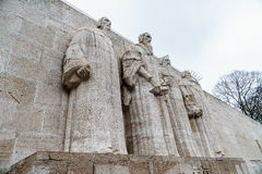 Reformation wall in Geneva. Statues on Reformation wall in Geneva, Switzerland. From left to right: William Farel, John Calvin, Theodore de Beze and John Knox Royalty Free Stock Photography