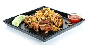 Reforços de carne de porco fritados com o alho isolado no fundo branco Fotos de Stock Royalty Free