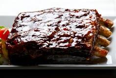 Reforços de carne de porco vitrificados com salada e as batatas cozidas Imagens de Stock