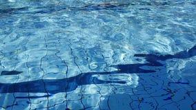 Refracción de la luz del sol en agua de la piscina metrajes
