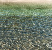 Refraction of light in clear water with small waves. Background Royalty Free Stock Photo