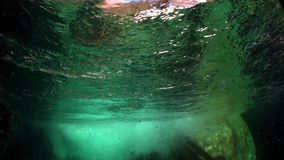 Refraction of sunlight underwater on smooth stones of river Verzasca.