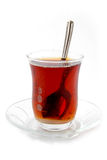 Refraction in tea. A cup of well steeped Turkish tea with teaspoon and saucer Royalty Free Stock Photography